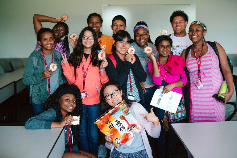A group of high school students pose with their Chinese-language instructor in a classroom.