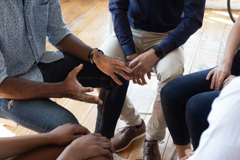 Closeup of people seated in a close circle for a group counseling session