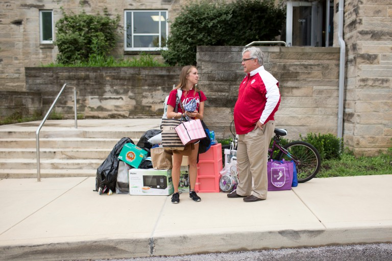 Dennis Groth stands with a student sidewalk outside a residence hall with things to move into a dorm