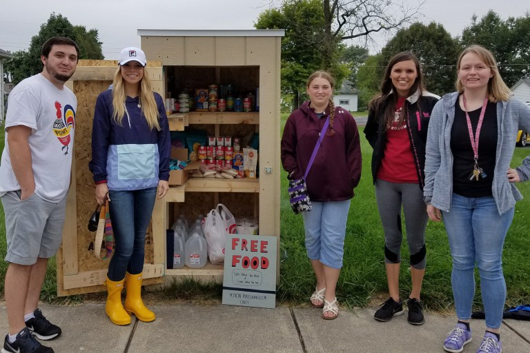 Students pose in front of a pantry of food.