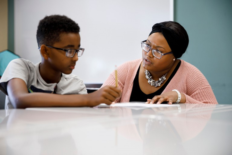 Chiara Logan helps a student work through a math problem at Fairview Elementary.