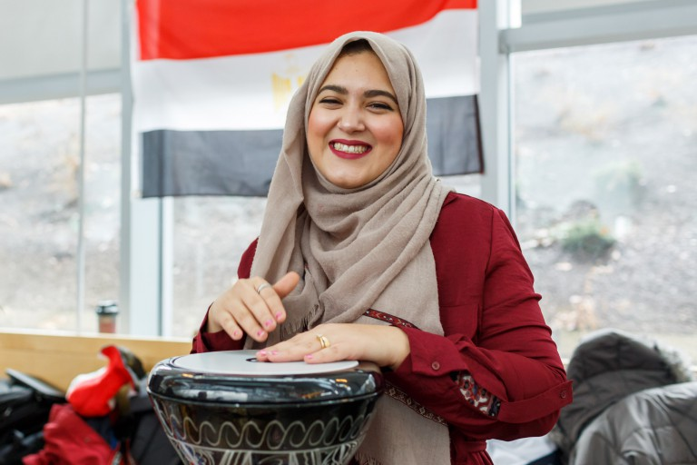 A student wearing a hijab, playing a drum at the International Festival