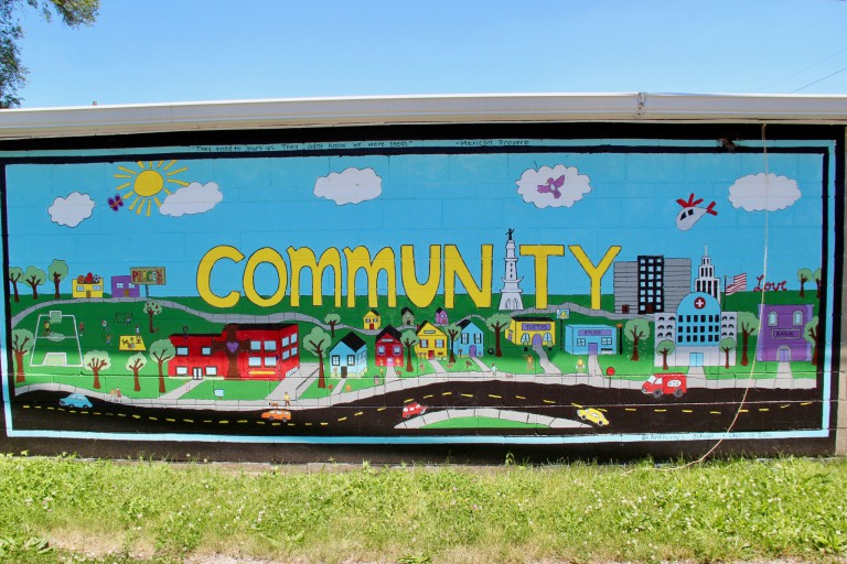 The word 'community' written on a wall mural