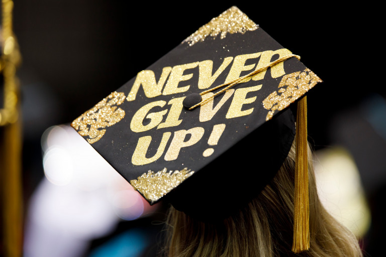 """A graduation cap reads """"Never give up."""""""