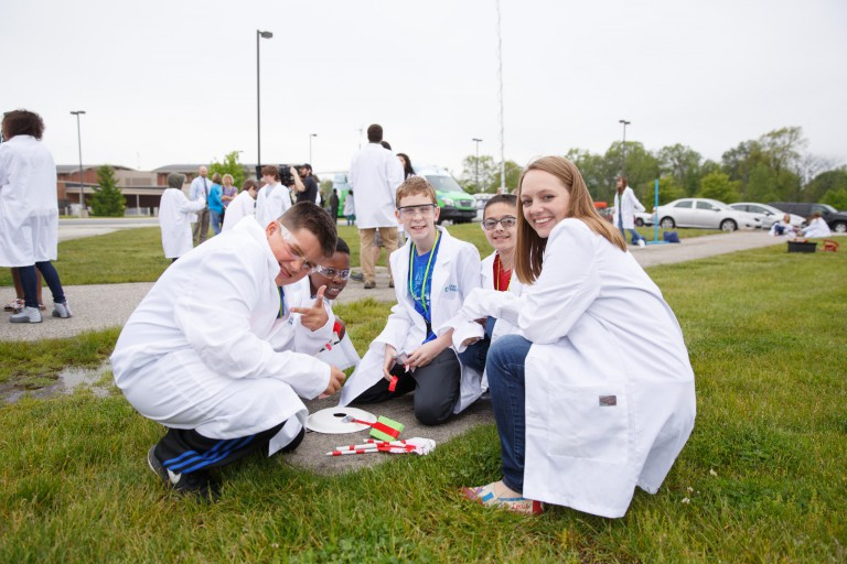 A group of middle school students in lab coats work on a hands-on science project.