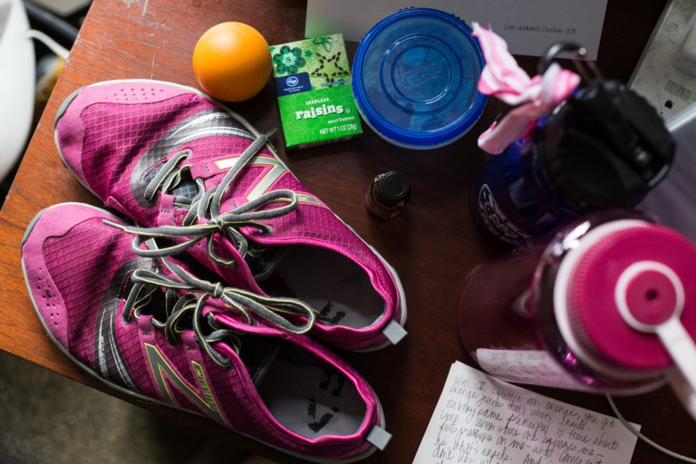 Elements of a healthy lifestyle: athletic shoes, a water bottle and healthy snacks