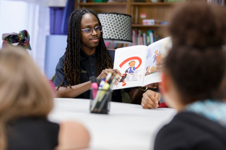 Tyler Kelley reads to young residents at The Rise