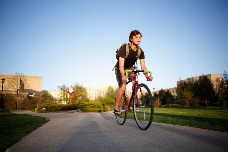 A male student wearing a backpack rides a bicycle along a paved path on a sunny day
