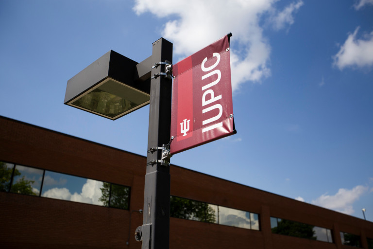 IUPUC banner attached to streetlight near a campus building