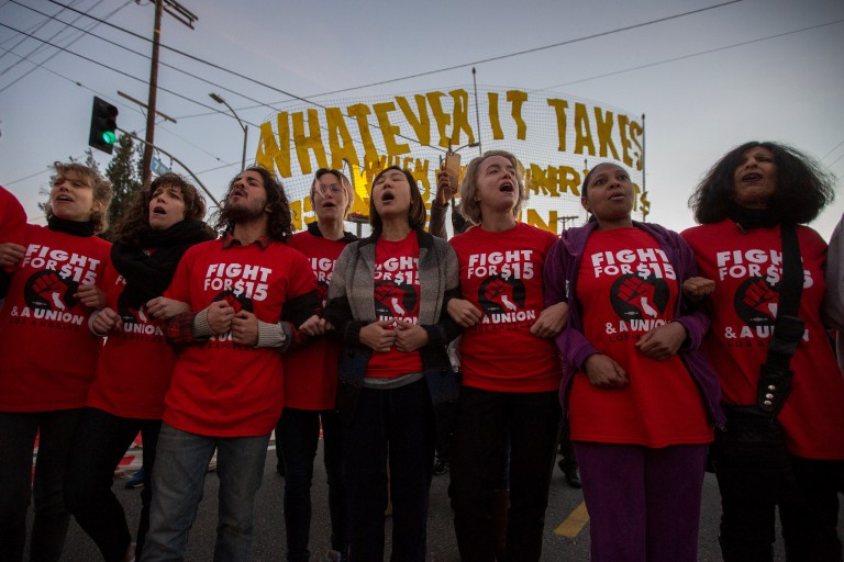 Workers rally for an increase in the minimum wage to $15 an hour.