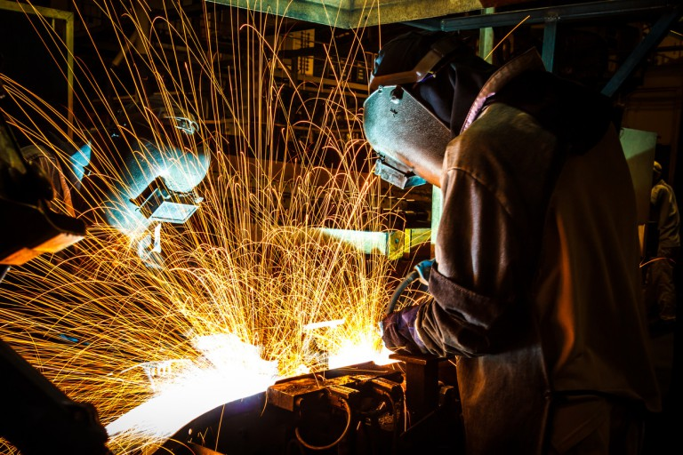 Sparks fly as workers weld pieces in the automotive industry.