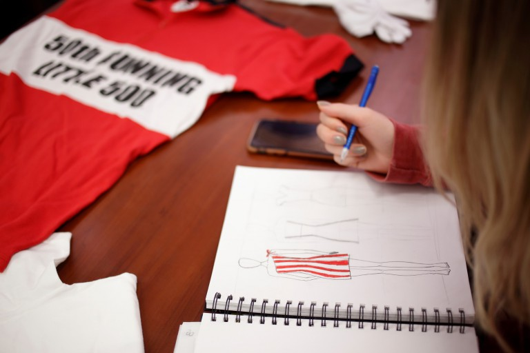 A student draws in a sketchbook next to a Little 500 jersey