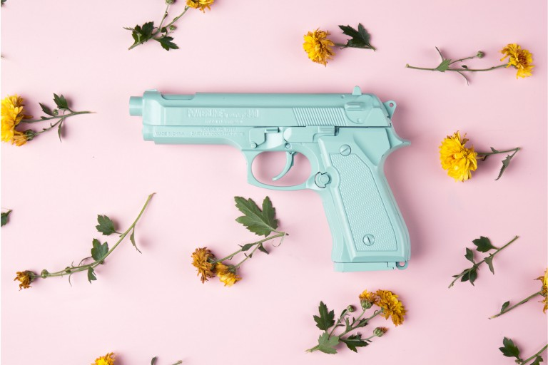 A teal colored gun on a pink background with flowers strewn about