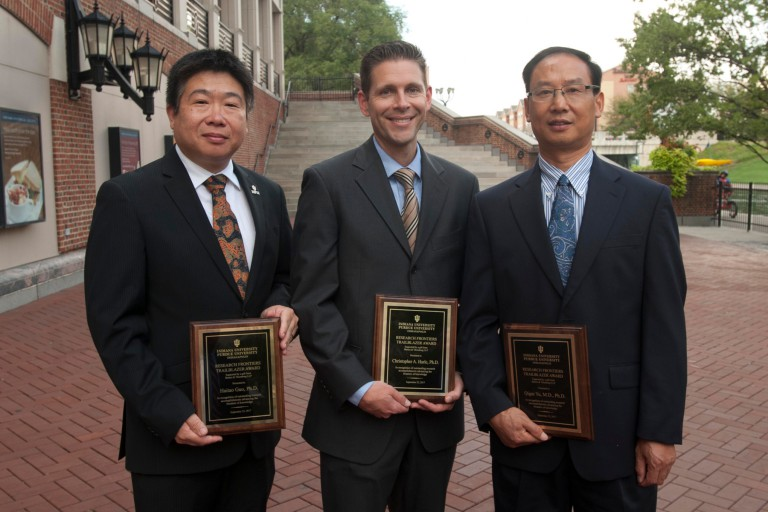 Haitao Guo, Chris Harle and Andy Yu hold their Research Frontiers Trailblazer Award plaques.