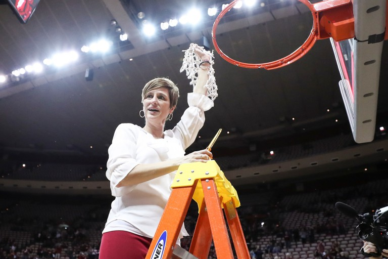 Teri Moren cutting the basketball net after winning the WNIT Championship.