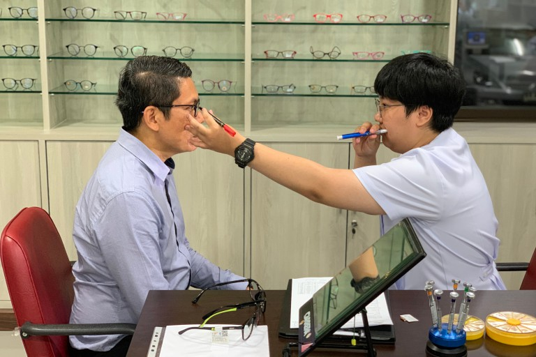 A student at Ramkhamhaeng University conducts an eye exam.