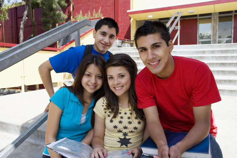 Four Latino teenagers hang out outside of a building
