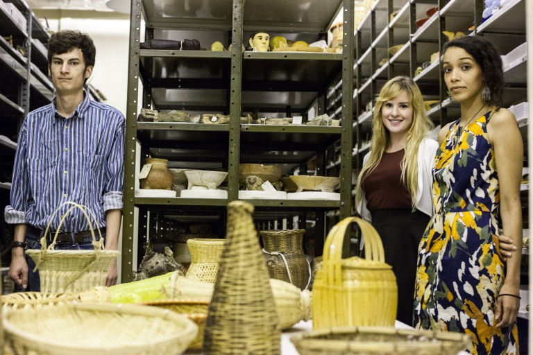Ethan Miller, Maggie Slaughter and Kaila Austin stand in collection storage surrounded by baskets