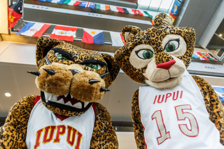 Jazzy and Jawz, two jaguar mascots, pose in the Campus Center