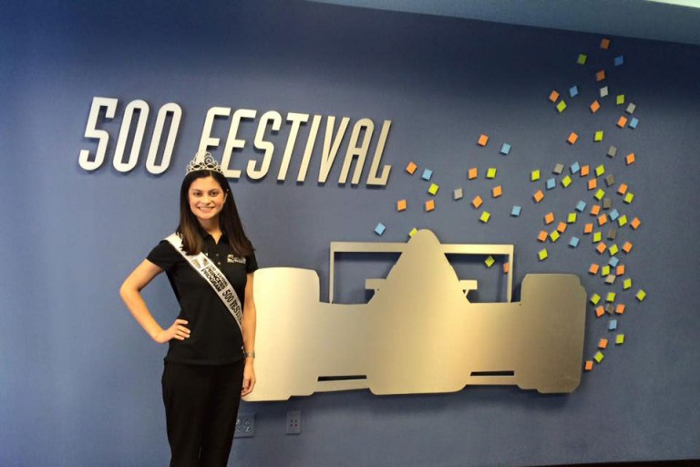 Amna Sohail stands in front of a blue wall with wall art depicting an Indy car for the 500 Festival
