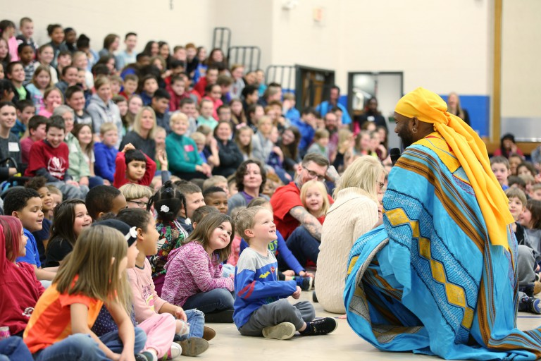 A member of the African American Dance company kneels to talk to children at Highland Park School.