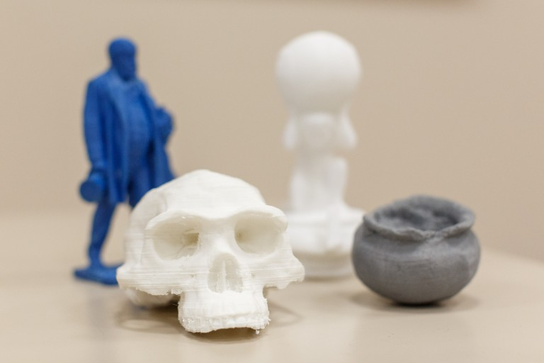 A series of 3D printed artifacts, including a skull and a pot