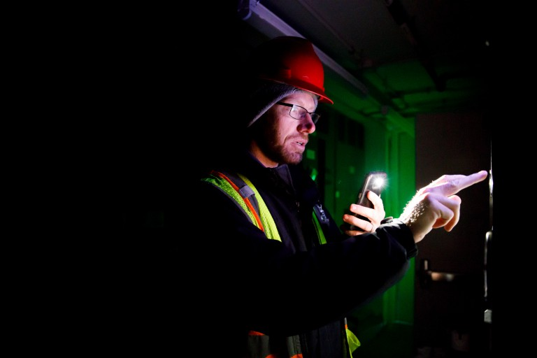 IU Bloomington Meter Data Analyst Ian Yarbrough reads a meter in the basement of Luddy Hall