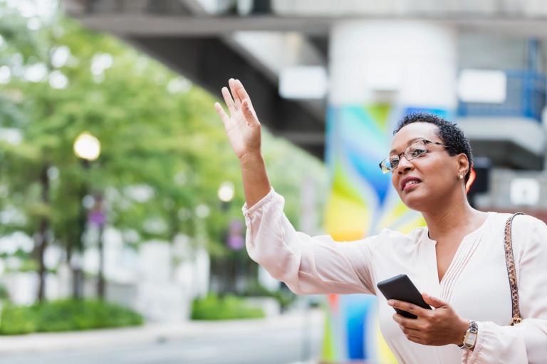 Woman raises her hand to hail a driver