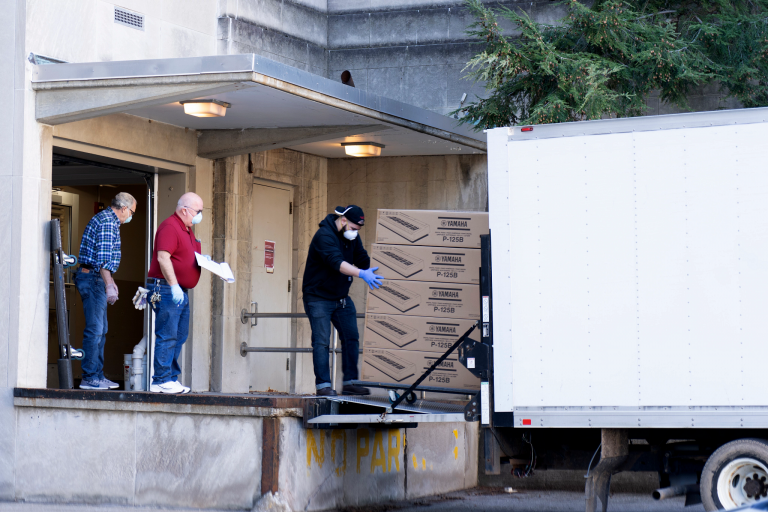 Gloved and masked workers move boxed Yamaha digital pianos from a truck to a loading dock.