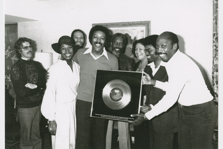 Group of people hold a framed gold record