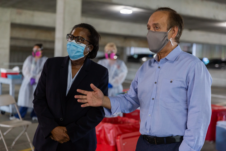Chancellor Nasser Paydar and Dr. Virginia Caine observe COVID-19 testing in an IUPUI garage