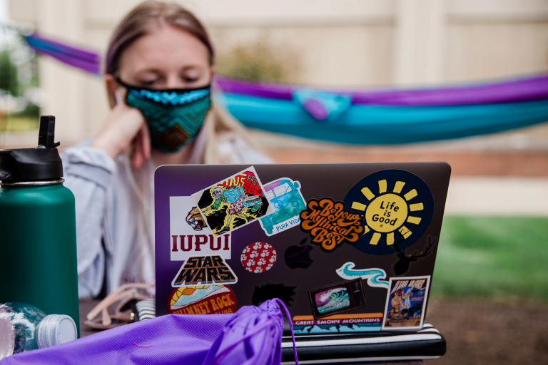 IUPUI student studying at a laptop covered in stickers