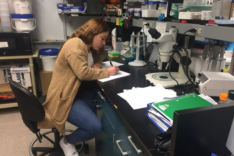 Female student taking notes in a science lab