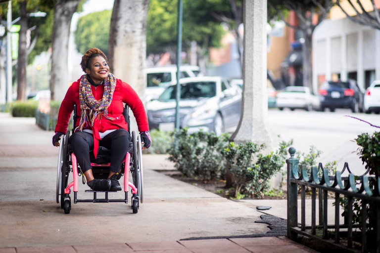 A woman uses a wheelchair on a city sidewalk