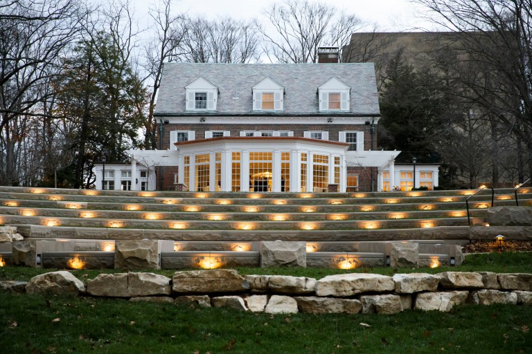 Amphitheater lit up at night with the Bryan House in the background