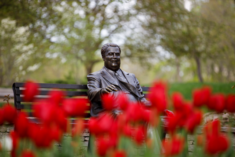 The Herman B Wells statue with a blur of red tulips in the foreground