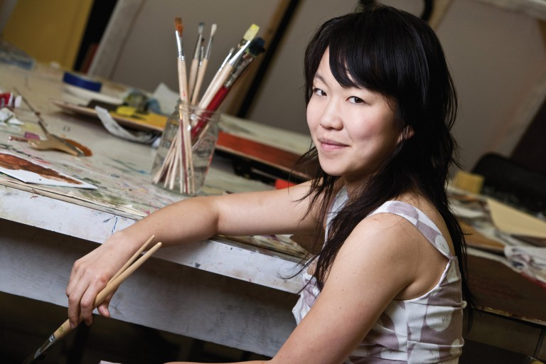 Ann Kim holding a paint brush in her hand in front of a painting table
