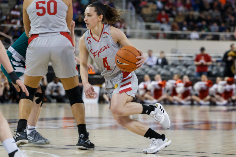 a woman dribbles a basketball during a game