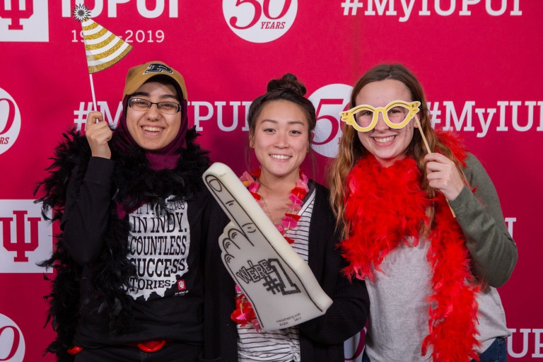 Students use funny props to pose in a photo booth