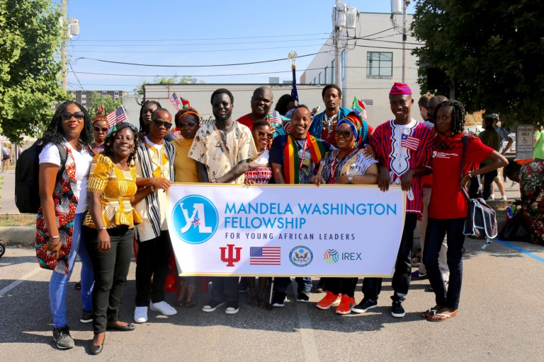 A group of Mandela Fellows hold a banner with the program's name and logos for the partners.