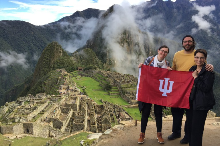 Janice poses with her two children and an IU flag with Machu Picchu in the background