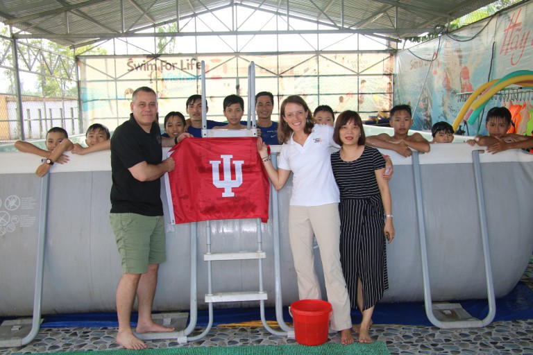 Bill Ramos and IU alum Beth Kreitl hold an IU flag at a pool in Vietnam.