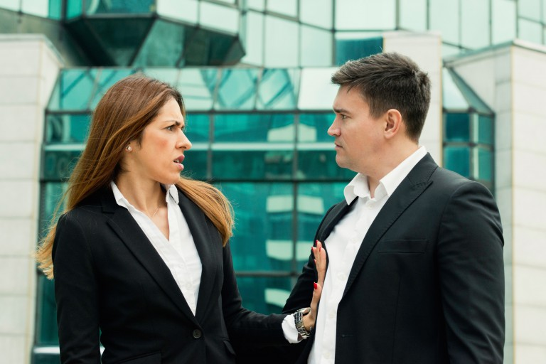 Woman pushing man away, both in business attire