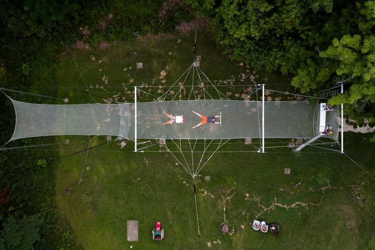 Two trapeze artists are soaring in the air over a large trapeze rig
