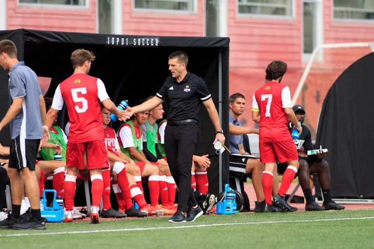 Soccer coach high-fives players on the sidelines of a game