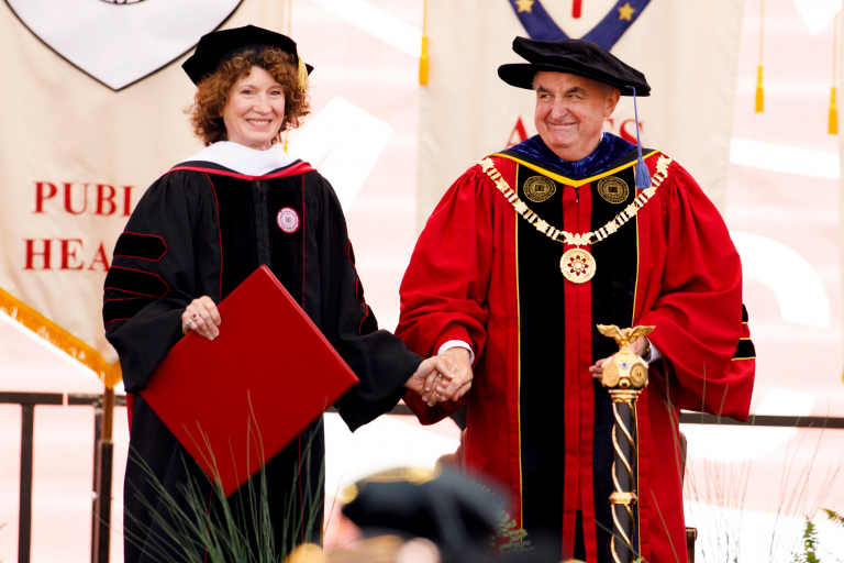 Laurie Burns McRobbie and Michael A. McRobbie stand on stage dressed in graduation robes