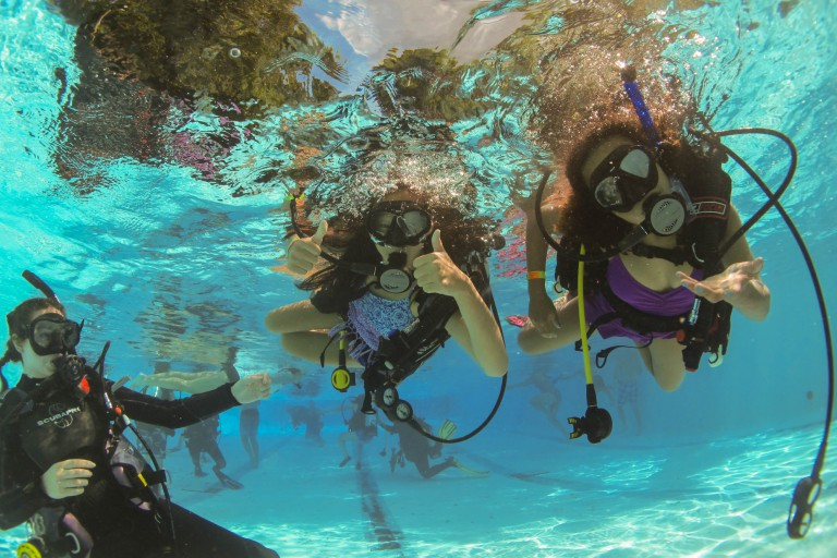 Two girls and their instructor swim underwater with scuba equipment