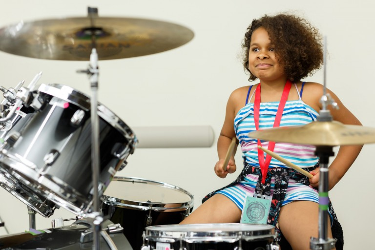 A girl plays drums at Girls Rock summer camp.