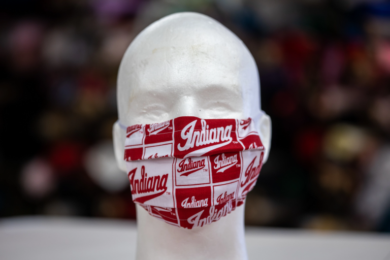 a mannequin head wears a red and white facemask with the word Indiana on it