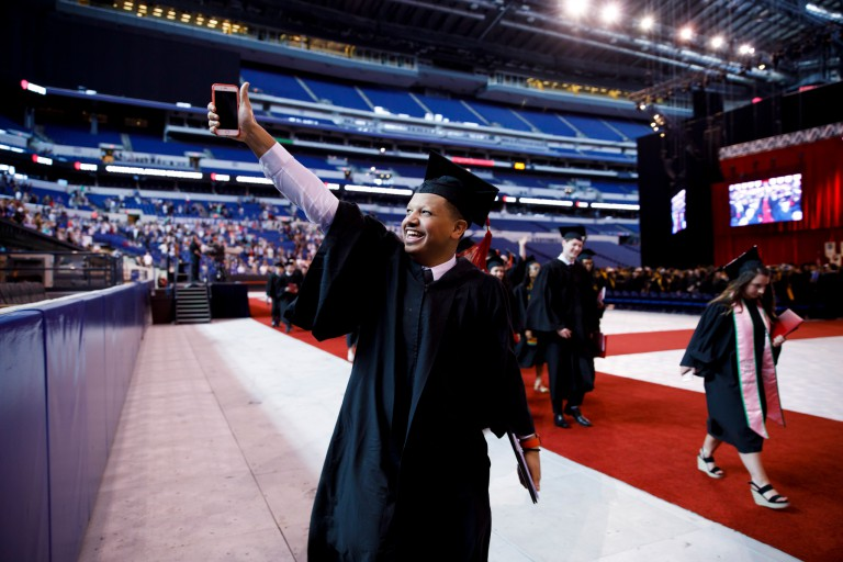 A graduate gives a thumbs-up after receiving his degree.